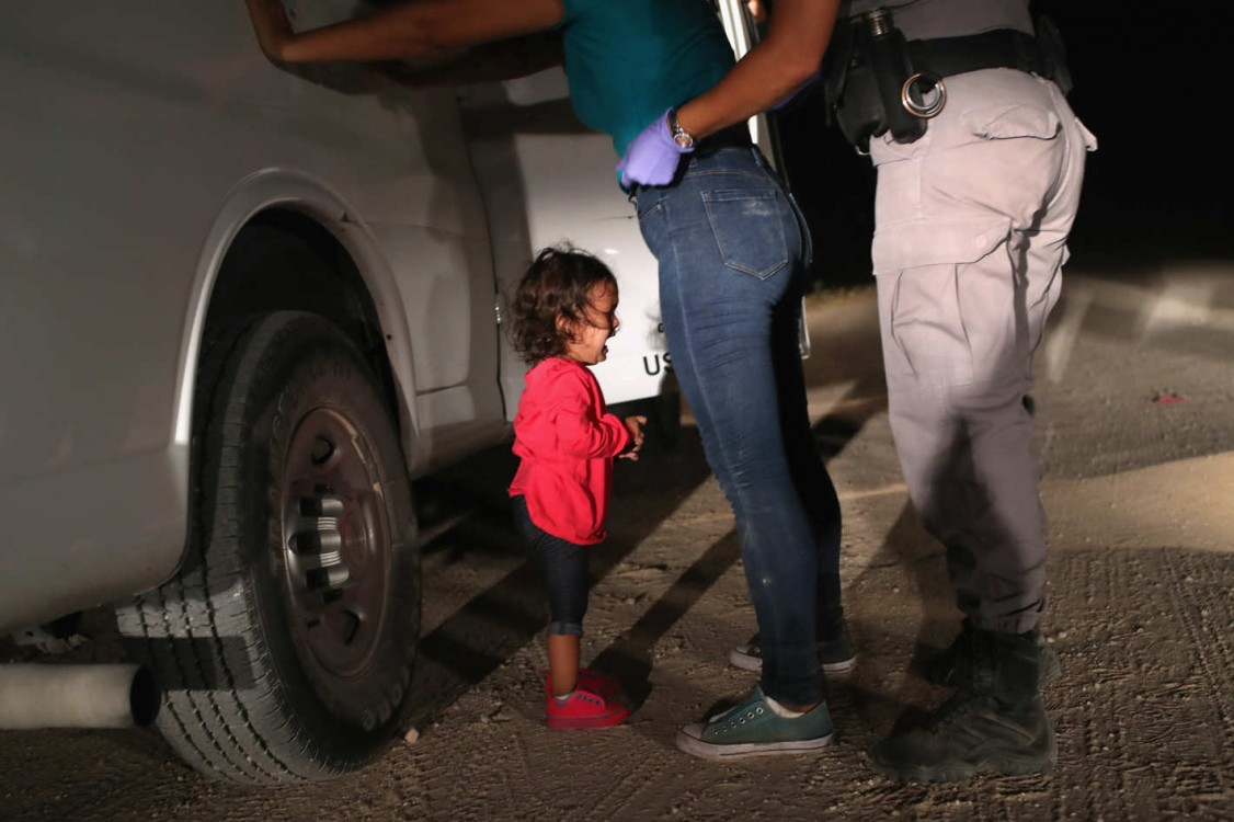 A 2-year-old Honduran asylum seeker cries as her mother is searched and detained near the U.S.-Mexico border on June 12, 2018, in McAllen, Texas. The asylum seekers had rafted across the Rio Grande from Mexico and were detained by U.S. Border Patrol agent