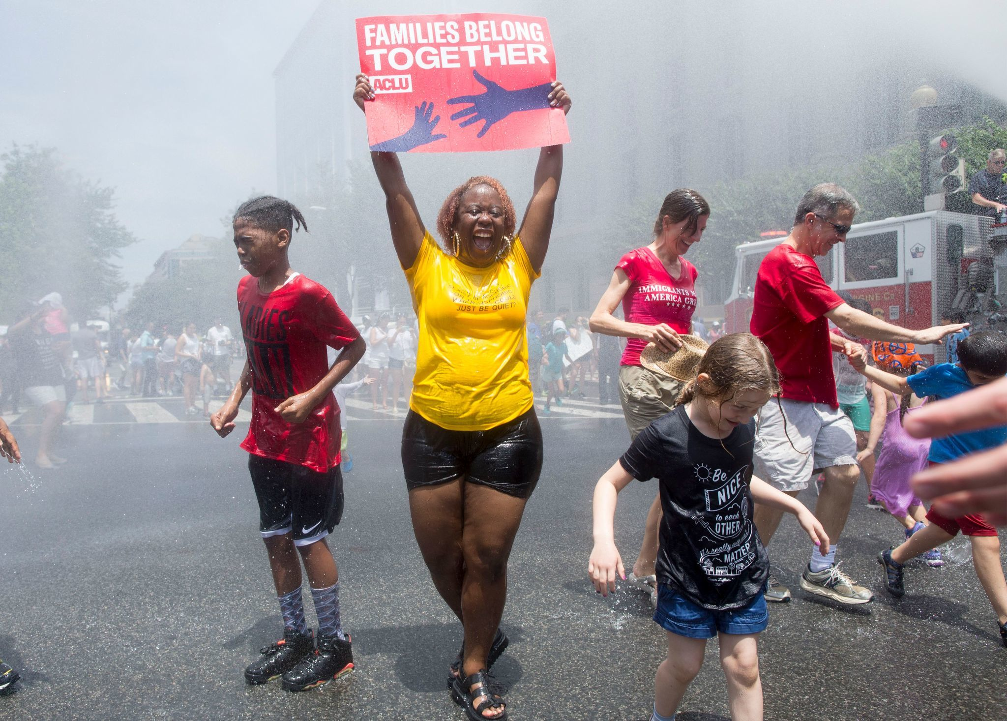 WASHINGTON, D.C.: A woman holds a sign while joining others underneath water being sprayed by a firetruck to cool off people attending a Families Belong Together rally. Michael Reynolds / EPA / Shutterstock