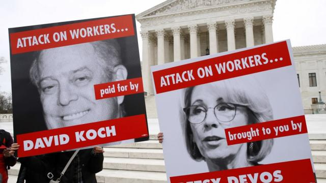Members of the American Federation of Teachers hold up signs depicting Education Secretary Betsy DeVos and David Koch, while protesting in support of unions outside of the supreme court on 26 February. Photograph: Jacquelyn Martin/AP